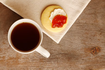 Tea or coffee time! Bird's eye view of tea or coffee with a sweet cookie or biscuit topped with cream and jam.