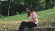 a young woman reading a Bible outdoors