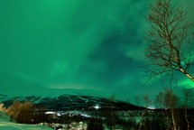 time-lapse of the northern lights with clouds moving over a mountain and lights in a city at night