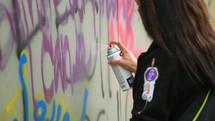 people spray painting graffiti on wall
