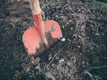 A red shovel  digging some dirt