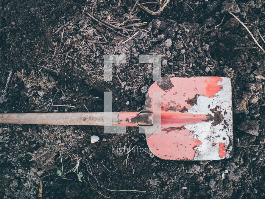 a red shovel sitting on dirt ready to be dug