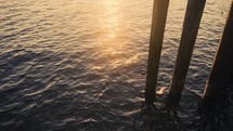 ocean water under a pier at sunset