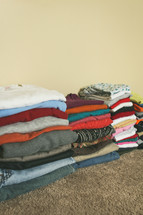 Stacks of folded clothes on the floor