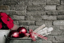 An arrangement of Christmas decorations against the backdrop of a gray brick wall.