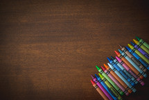row of crayons on a wood table