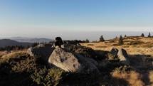 man kneeling in prayer on a mountaintop