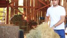 a farmer moving hay bales