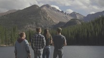 young people walking to the edge of a lake to take in the view of mountains