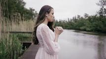 Woman praying on the lakeshore