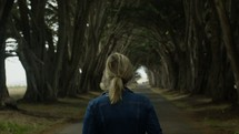 a woman walking down the middle of a tree lined road