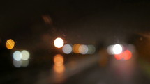 bokeh taillights from cars on a wet road at night