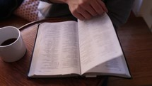 man reading a Bible with coffee
