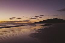 A purple sunset on beach shoreline.