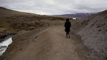 a woman in a coat walking on a dirt path