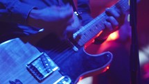 man strumming a guitar at a concert