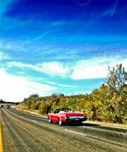Red corvette on highway