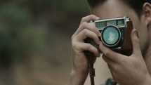 a man adjusting the lens of a camera