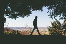 Silhouetted man walking in Tuscany