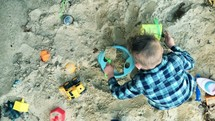 a boy child playing with sand toys in a sandbox