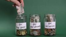 hands diving money between jars to do good