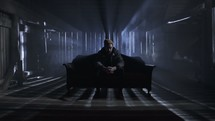 man sitting alone on a couch in a dark room