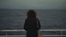 a woman on a ferry looking out at the water