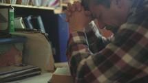 a man praying at his desk