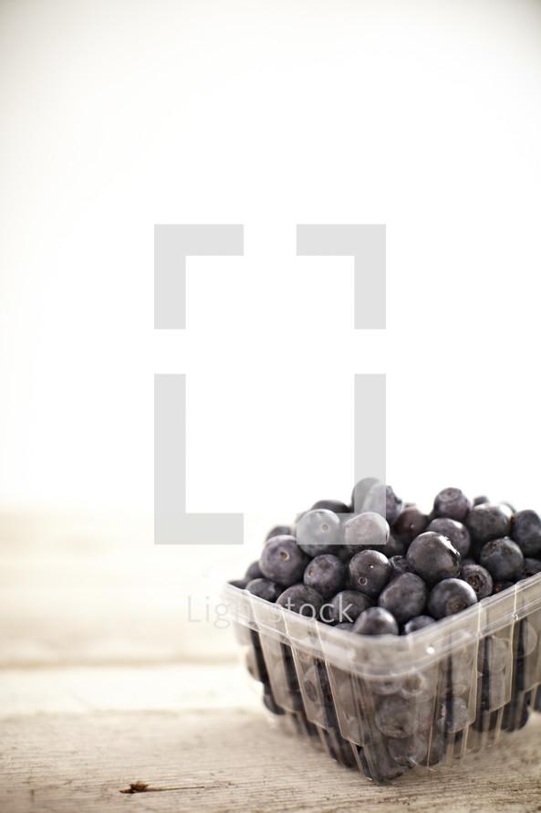 Carton of blueberries sitting on wood