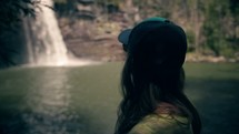 a woman looking out at a waterfall