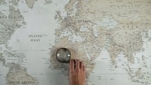 a person holding a magnifying glass over a world map