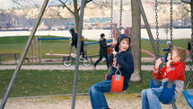 Two young boys having fun on a swing set in a city park.