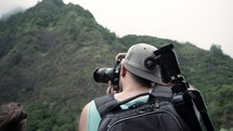 a man with a camera photographing a mountain