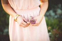 a woman holding purple flowers