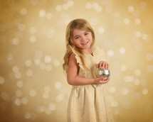 A light girl holding a Christmas ornament
