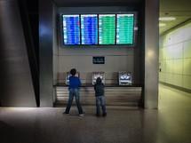 kids at an airport looking up at flights