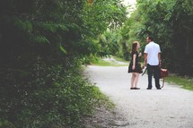 a couple standing on a dirt road