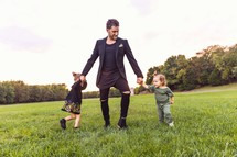 father dancing with his girls in a grassy field