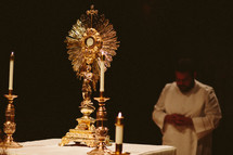Priest bowing before the Monstrance at Eucharist adoration in a Catholic church .