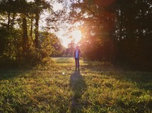 man standing in a forest clearing under intense sunlight