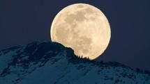 moon rising behind a mountain peak