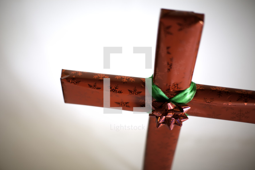 Red wrapped present shaped like a cross with red and green bow in the center.