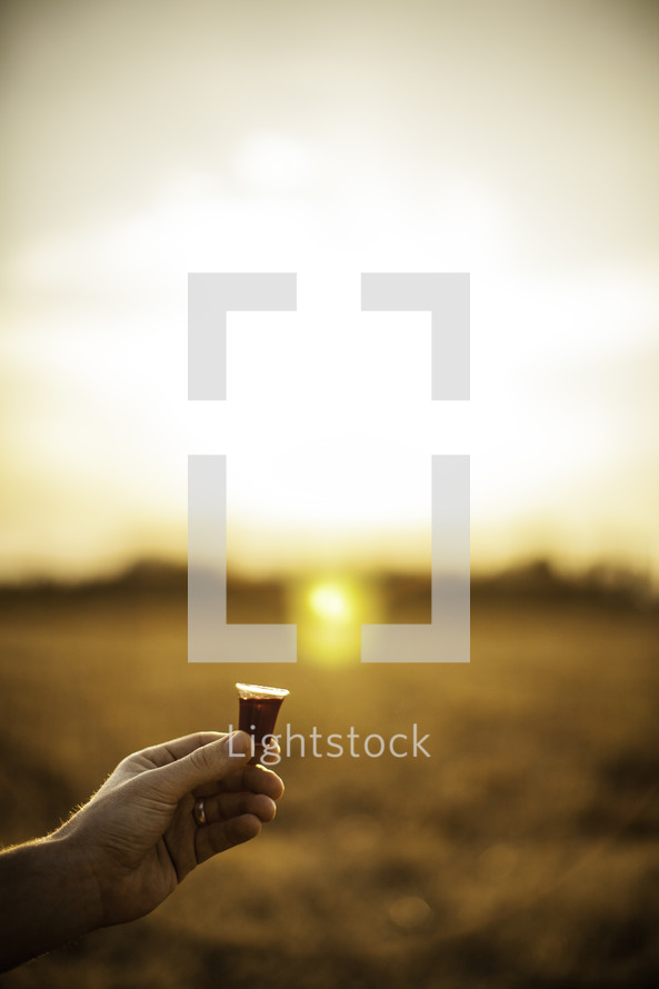 outside communion - hand holding communion wine