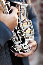 playing a silver alto saxophone man holding