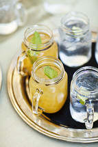 Drinks sitting on a tray lemonade and ice water mason jars