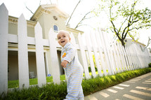 toddler walking on a sidewalk in front of a picket fence