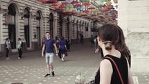 people walking on a cobblestone street between shops
