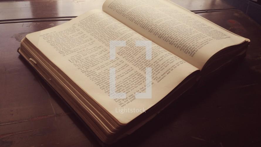 Open Bible lying on an antique desk