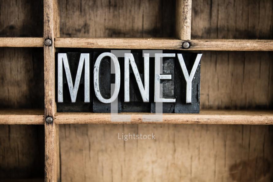 word money in blocks on a bookshelf
