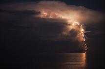 lighting in a night sky over the ocean